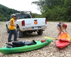 Two people unloading kayaks to float the river