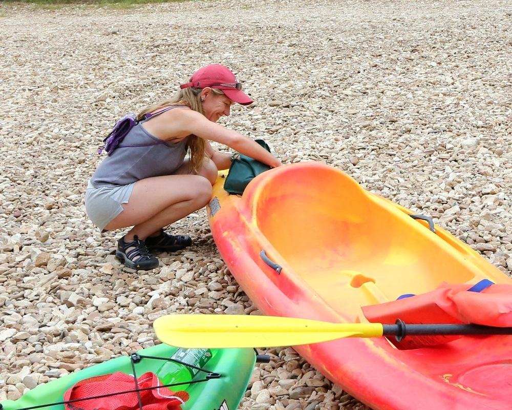 Woman getting kayak ready for floating