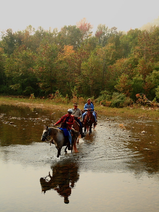 3 people riding horses in the river